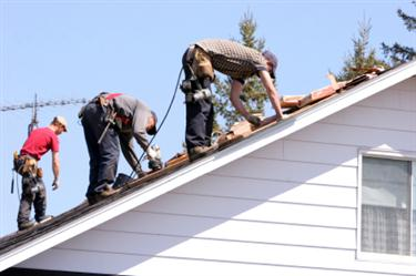 Roof Installation in Pollok TX. Three roofers laying new shingle on a roof in Pollok.